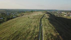 走在领域鸟瞰图的日落夏天晚上的青年人夫妇  股票录像