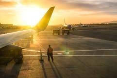 走在飞机翼附近的工人在机场终端 免版税库存照片