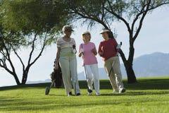 走在高尔夫球场的妇女 图库摄影
