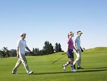 走在高尔夫球场的高尔夫球运动员 免版税库存照片