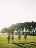走在高尔夫球场的高尔夫球运动员 免版税库存图片