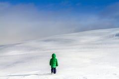 走在高山的云彩附近的一个冒险的小男孩 免版税库存图片