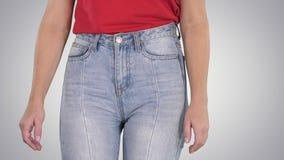 走在高牛仔裤和红色T恤杉的偶然妇女在梯度背景 股票视频