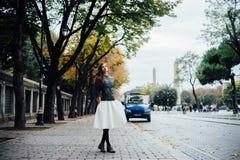 走在鹅卵石正方形的美丽的女孩 古老区域秋天 库存照片