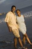 走在水中的夫妇在海滩 免版税库存图片