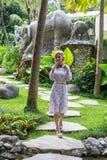 走在巴厘岛,印度尼西亚一个热带庭院里的妇女  库存照片