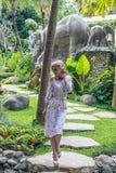 走在巴厘岛,印度尼西亚一个热带庭院里的妇女  免版税库存图片