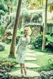 走在巴厘岛,印度尼西亚一个热带庭院里的妇女  库存图片