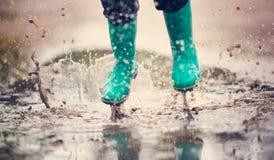 走在水坑的wellies的孩子在多雨天气 图库摄影
