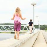 走在水坝栏杆的孩子  免版税库存图片