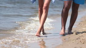 走在水域中的脚特写镜头在海滩渐近 股票录像