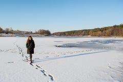 走在冻多雪的河的一根年轻美丽的红色头发的画象在森林附近 免版税图库摄影