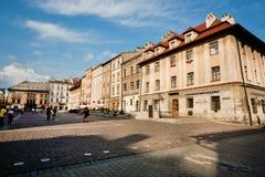 走在晴天的长的阴影的人们在波兰城市的中心 库存图片