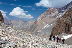 走在离开的岩石地形的小组远足者 免版税库存照片