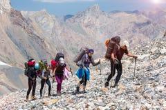 走在离开的岩石地形的小组远足者 图库摄影
