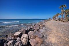 走在2016年2月23日的美洲日报海岸线的游人在阿德赫,特内里费岛,西班牙 免版税图库摄影