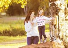 走在晴朗的秋天的愉快的母亲和女儿孩子 免版税库存照片
