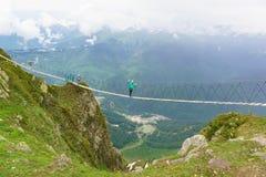 走在索桥的三个游人舒展了在峡谷对滑雪胜地 图库摄影