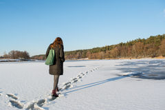 走在冻河的一根年轻美丽的红色头发的画象在森林附近 库存照片