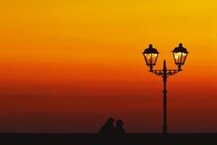 走在黑海海岸的日落的浪漫夫妇 库存图片