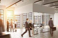 走在玻璃办公室的商人 明亮的阳光 办公室生活的概念 免版税库存照片