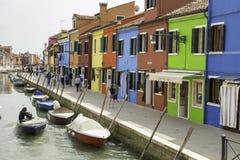 走在Burano市五颜六色的街道上的游人有小船和传统房子的临近盐水湖 免版税库存照片