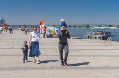 走在Dripro河堤防的父亲、母亲和两个孩子春天晴朗的周末 库存图片