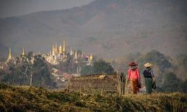 走在Inle湖岸的妇女在与一座塔的Nampan市场上在背景, Inle湖,掸邦,缅甸中 库存图片