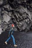 走在Kirkjufjara黑色沙子海滩,南冰岛的妇女 库存图片