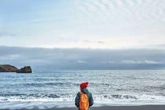 走在Kirkjufjara黑色沙子海滩,南冰岛的妇女 免版税库存照片