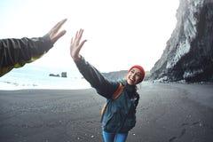 走在Kirkjufjara黑色沙子海滩,南冰岛的妇女 库存照片