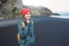 走在Kirkjufjara黑色沙子海滩,南冰岛的妇女 免版税库存图片
