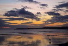 走在Lahinch的夫妇在日落靠岸 库存图片