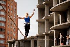 走在slackline绳索的背面图女孩到未完成的大厦 库存照片