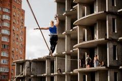 走在slackline绳索的背面图妇女到未完成的大厦 图库摄影