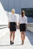 走在stre的两个年轻可爱的女商人背面图  免版税库存照片
