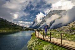 走在Trollstigen,挪威附近的少妇 免版税库存照片
