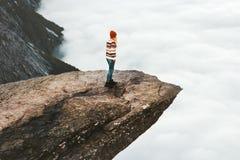 走在Trolltunga岩石峭壁的妇女探险家在挪威 免版税库存照片
