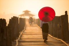走在U Bein桥梁的未认出的缅甸妇女 库存图片