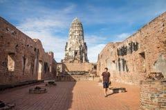 走在Wat Ratchaburana寺庙附近的一个男性旅客在阿尤特拉利夫雷斯历史公园, Phra洛坤Si大城府,泰国 免版税库存图片