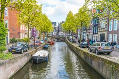 走地方和游人在一条小阿姆斯特丹运河的在春天在与小船、自行车和汽车的Jordaan地区 免版税图库摄影
