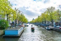 走地方和游人在Keizersgracht运河的在春天在与小船、自行车和汽车的Jordaan地区 免版税库存照片
