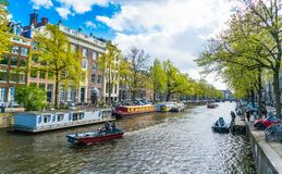 走地方和游人在Keizersgracht运河的在春天在与小船、自行车和汽车的Jordaan地区 库存照片