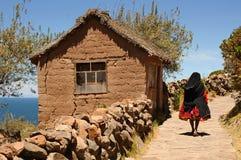 走地方的妇女一条上升的道路在典型的Taquile海岛环境美化, Titicaca湖,秘鲁 免版税图库摄影