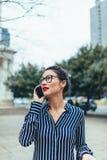 走外面使用手机的亚裔女实业家 免版税库存图片