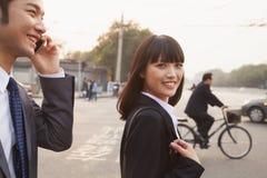 走外面在街道上的两个微笑的年轻商人在北京,谈话在电话 免版税库存照片