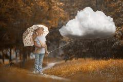 走多雨云彩的女孩在橙色背景的秋天时间 免版税库存图片