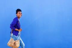 走对蓝色墙壁的微笑的年轻非洲妇女 免版税库存照片