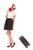 走带着台车手提箱的女实业家。 免版税库存照片