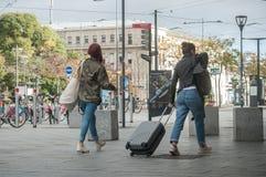 走带着在火车站前面的手提箱的妇女 库存图片